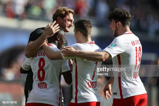 Naby Keitab of Leipzig celebrates with head coach Ralph Hasenhuettl and his team mates after scoring a goal to make it 10 the Bundesliga match...
