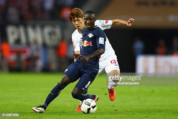 Naby Keïta of RB Leipzig battles for the ball with Yuya Osako of Koeln during the Bundesliga match between 1 FC Koeln and RB Leipzig at...
