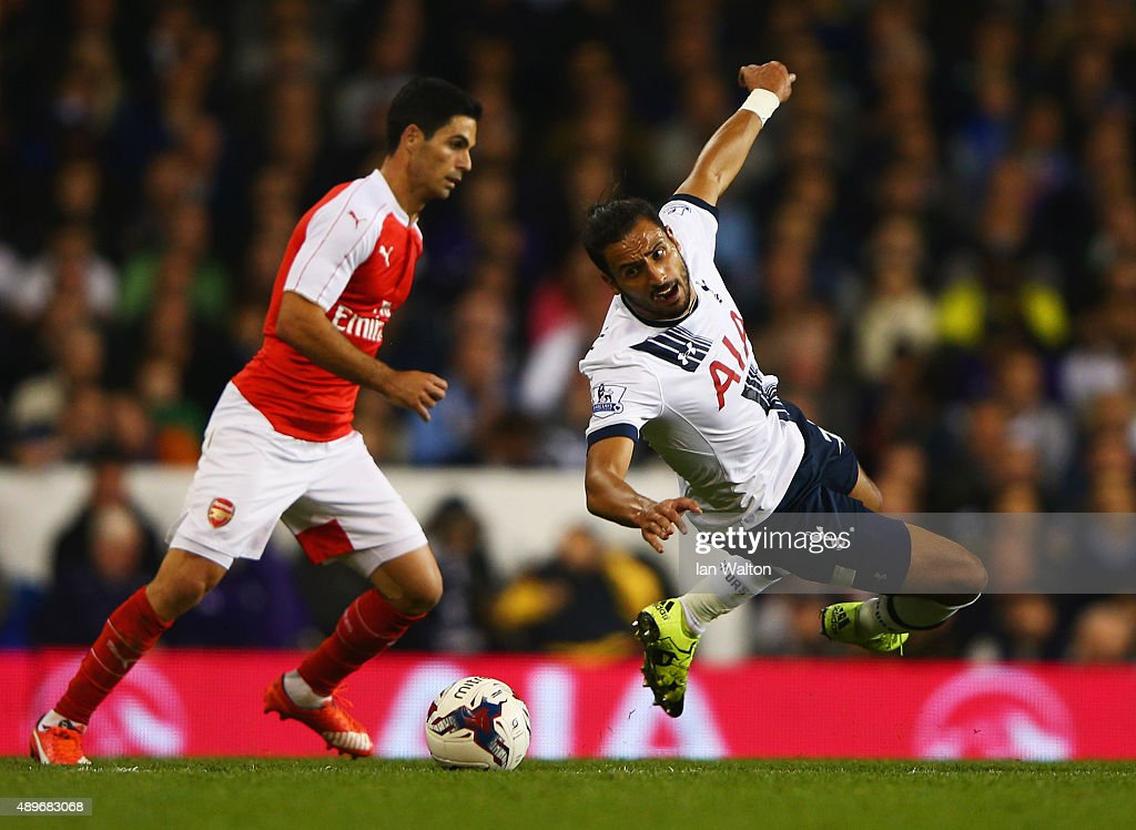 Nacer Chadli of Tottenham Hotspur battles with Mikel Arteta of Arsenal during the Capital One Cup third round match between Tottenham Hotspur and Arsenal at White Hart Lane on September 23, 2015 in London, England.