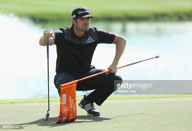 Nacho Elvira of Spain lines up a putt on the ninth green during the completion of the weather delayed second round of the Omega Dubai Desert Classic...