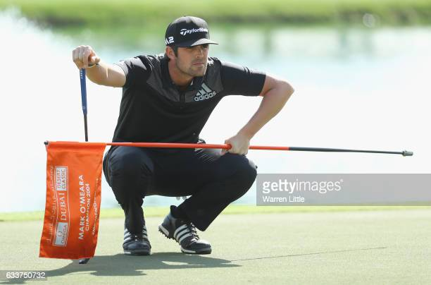 Nacho Elvira of Spain lines upa putt on the ninth green during the completion of the weather delayed second round of the Omega Dubai Desert Classic...