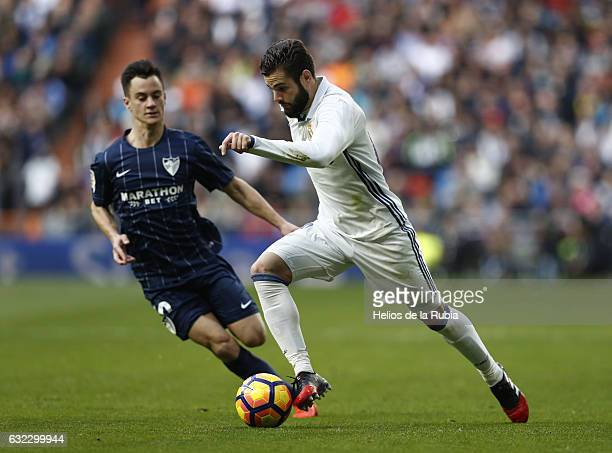Nacho Fernandez of Real Madrid and Juanpi of Malaga CF compete for the ball during the La Liga match between Real Madrid and Malaga CF at Estadio...