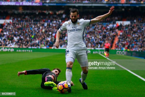 Nacho Fernandez of Real Madrid CF competes for the ball with David Lopez of RCD Espanyol during the La Liga match between Real Madrid CF and RCD...