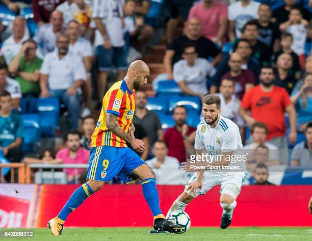 Nacho Fernandez of Real Madrid fights for the ball with Simone Zaza of Valencia CF during their La Liga 201718 match between Real Madrid and Valencia...