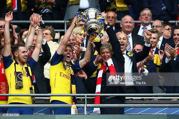 Nacho Monreal of Arsenal and Arsene Wenger manager of Arsenal lift the trophy after the FA Cup Final between Aston Villa and Arsenal at Wembley...