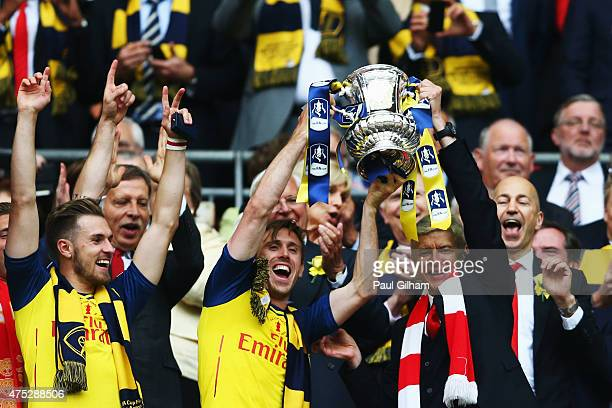 Nacho Monreal of Arsenal and Arsene Wenger manager of Arsenal lift the winners trophy following the FA Cup Final between Aston Villa and Arsenal at...