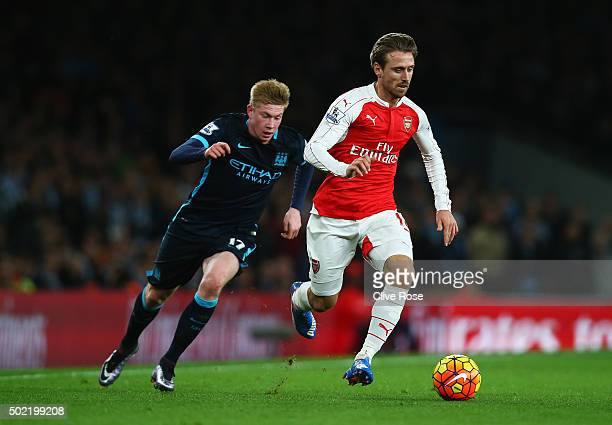 Nacho Monreal of Arsenal goes past Kevin de Bruyne of Manchester City during the Barclays Premier League match between Arsenal and Manchester City at...