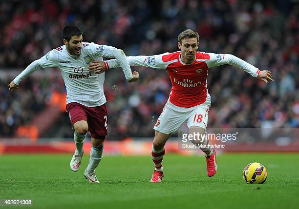 Nacho Monreal of Arsenal holds off Carles Gil of Aston Villa during the Barclays Premier League match between Arsenal and Aston Villa at Emirates...