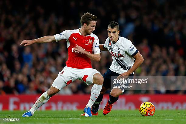 Nacho Monreal of Arsenal holds off Erik Lamela of Spurs during the Barclays Premier League match between Arsenal and Tottenham Hotspur at the...