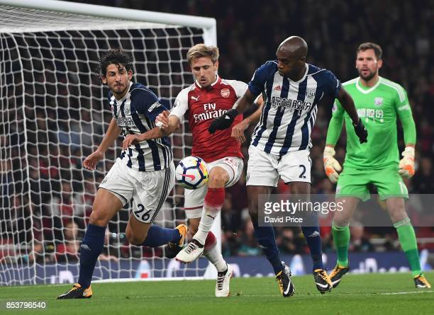 Nacho Monreal of Arsenal is challenged by Ahmed Hegazy and Allan Nyom of West Bromwich during the Premier League match between Arsenal and West...