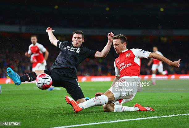Nacho Monreal of Arsenal is closed down by James Milner of Liverpool during the Barclays Premier League match between Arsenal and Liverpool at...