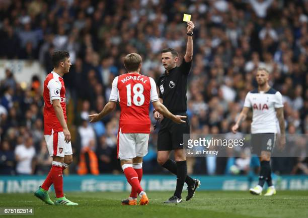 Nacho Monreal of Arsenal is shown a yellow card by referee Michael Oliver during the Premier League match between Tottenham Hotspur and Arsenal at...