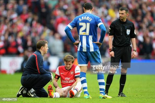 Nacho Monreal of Arsenal is taken off injured as Ivan Ramis of Wigan Athletic looks on during the FA Cup SemiFinal match between Wigan Athletic and...