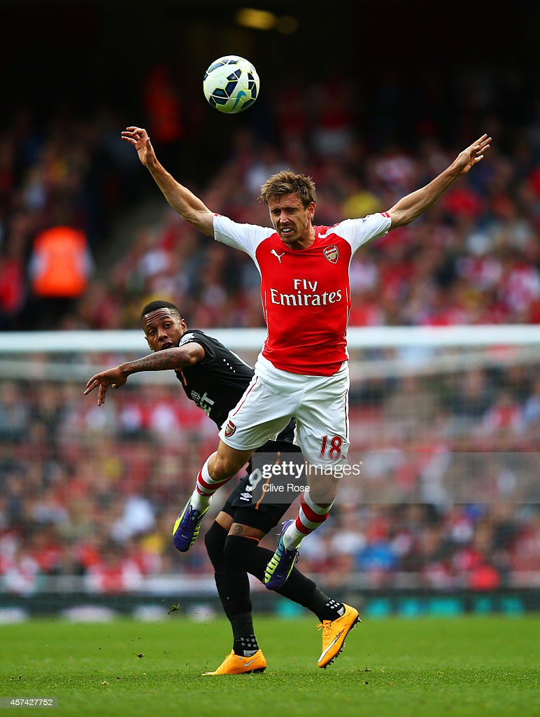 Nacho Monreal of Arsenal jumps for the ball with Abel Hernandez of Hull City during the Barclays Premier League match between Arsenal and Hull City at Emirates Stadium on October 18, 2014 in London, England.