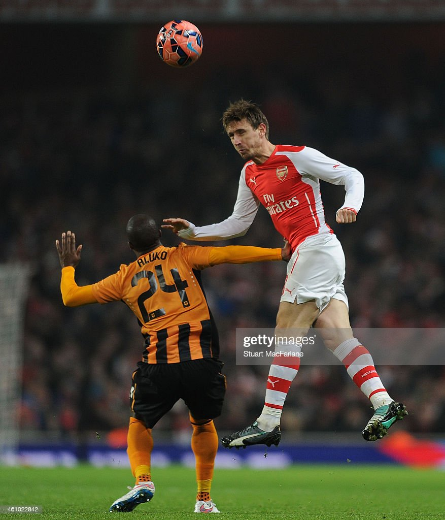 Nacho Monreal of Arsenal outjumps Sone Aluko of Hull during the FA Cup Third Round match between Arsenal and Hull City at Emirates Stadium on January 4, 2015 in London, England.