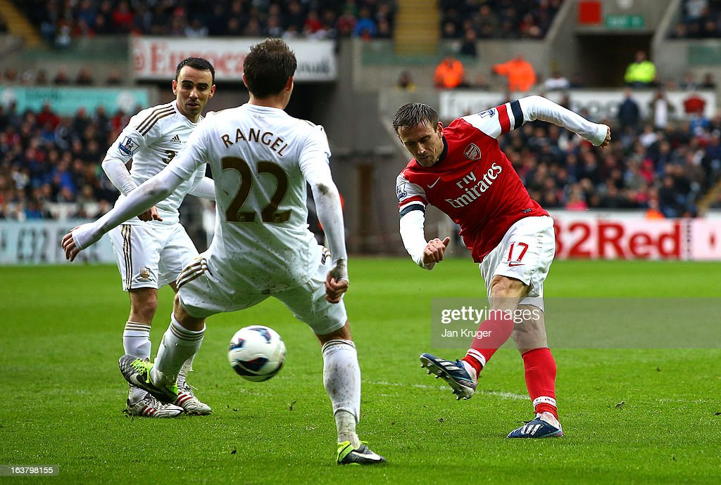 <a gi-track='captionPersonalityLinkClicked' href=/galleries/search?phrase=Nacho+Monreal&family=editorial&specificpeople=4078049 ng-click='$event.stopPropagation()'>Nacho Monreal</a> of Arsenal shoots past Angel Rangel of Swansea City for their first goal during the Barclays Premier League match between Swansea City and Arsenal at Liberty Stadium on March 16, 2013 in Swansea, Wales.