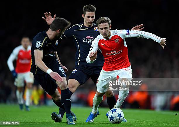 Nacho Monreal of Arsenal takes on Ivo Pinto of Dinamo Zagreb and Marko Pjaca of Dinamo Zagreb during the UEFA Champions League match between Arsenal...