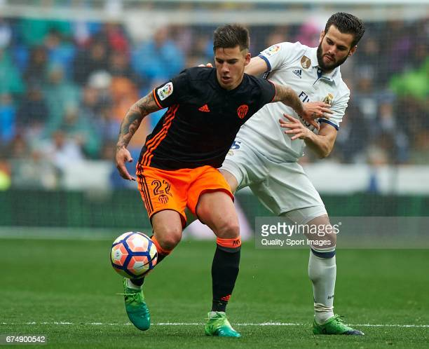 Nacho of Real Madrid competes for the ball with Santi Mina of Valencia during the La Liga match between Real Madrid CF and Valencia CF at Estadio...