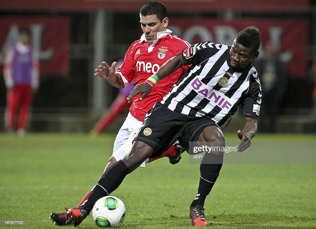 Nacional's Senegalese forward Keita (R) vies with Benfica's Uruguayan defender Maxi Pereira during the Portuguese league football match Nacional vs Benfica at Madeira stadium in Funchal on February 10, 2013.