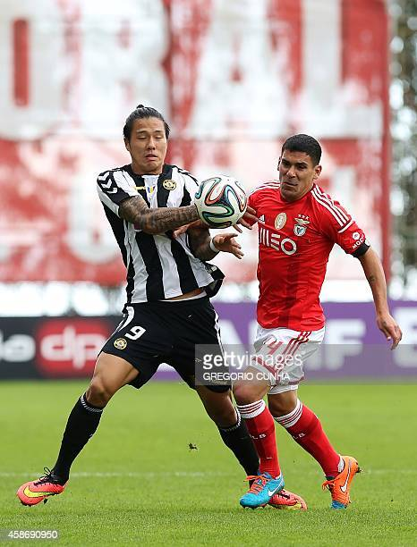 Nacional's South Korean forward Suk vies with Benfica's Uruguayan defender Maxi Pereira during the Portuguese league football match CD Nacional vs SL...