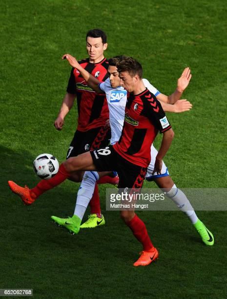Nadeem Amiri of Hoffenheim challenges Janik Haberer of Freiburg during the Bundesliga match between SC Freiburg and TSG 1899 Hoffenheim at...