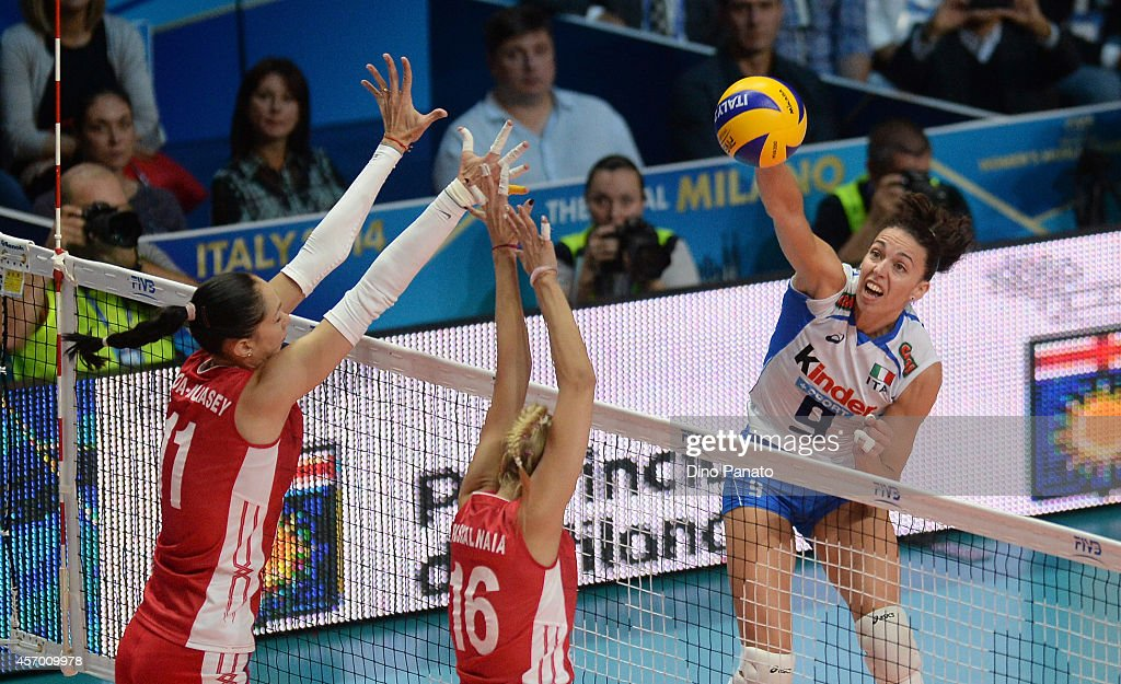 <a gi-track='captionPersonalityLinkClicked' href=/galleries/search?phrase=Nadia+Centoni&family=editorial&specificpeople=2309657 ng-click='$event.stopPropagation()'>Nadia Centoni</a> (R) of Italy spikes the ball against Ekaterina Gamova (L) and Yuliya Podskalnaya of Russia during the FIVB Women's World Championship pool H match between Italy and Russia on October 10, 2014 in Milan, Italy.