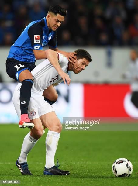 Nadiem Amiri of 1899 Hoffenheim challenges Xabi Alonso of Bayern Munich during the Bundesliga match between TSG 1899 Hoffenheim and Bayern Muenchen...