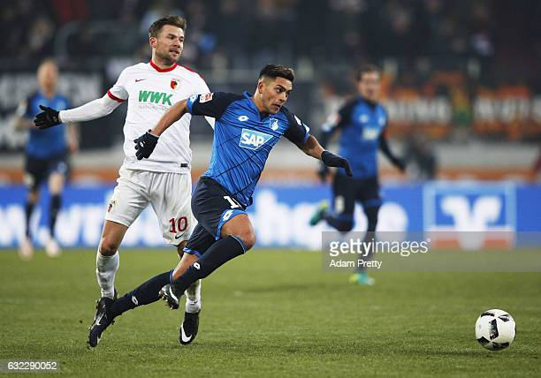 Nadiem Amiri of 1899 Hoffenheim is challenged by Daniel Baier of Augsburg during the Bundesliga match between FC Augsburg and TSG 1899 Hoffenheim at...