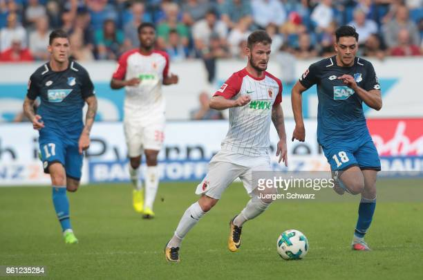 Nadiem Amiri of Hoffenheim follows Marcel Heller of Augsburg during the Bundesliga match between TSG 1899 Hoffenheim and FC Augsburg at Wirsol...
