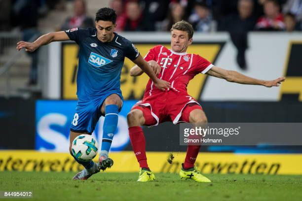Nadiem Amiri of Hoffenheim is challenged by Thomas Mueller of Muenchen during the Bundesliga match between TSG 1899 Hoffenheim and FC Bayern Muenchen...