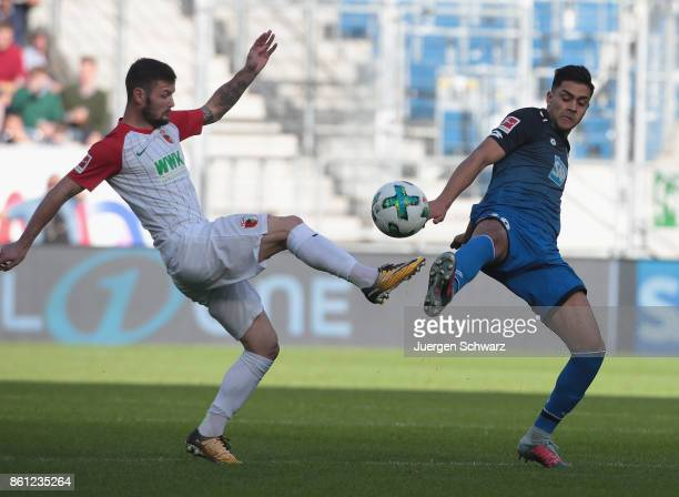 Nadiem Amiri of Hoffenheim tackles Marcel Heller of Augsburg during the Bundesliga match between TSG 1899 Hoffenheim and FC Augsburg at Wirsol...
