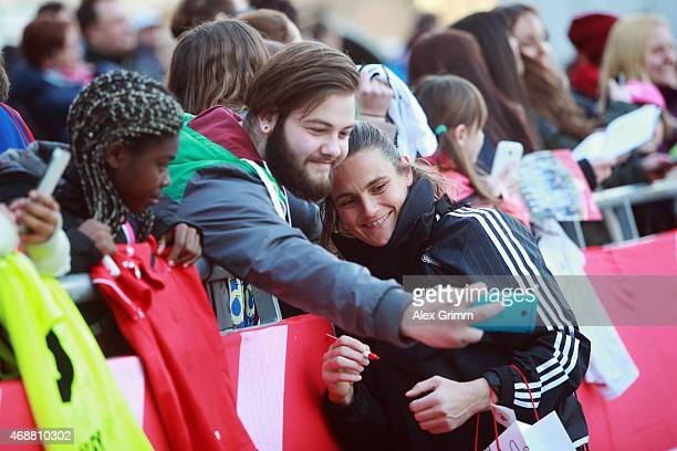 Nadine Angerer takes a photo with a fan during a Germany training session ahead of their friendly match against Brazil at Sportpark Ronhof on April 7...