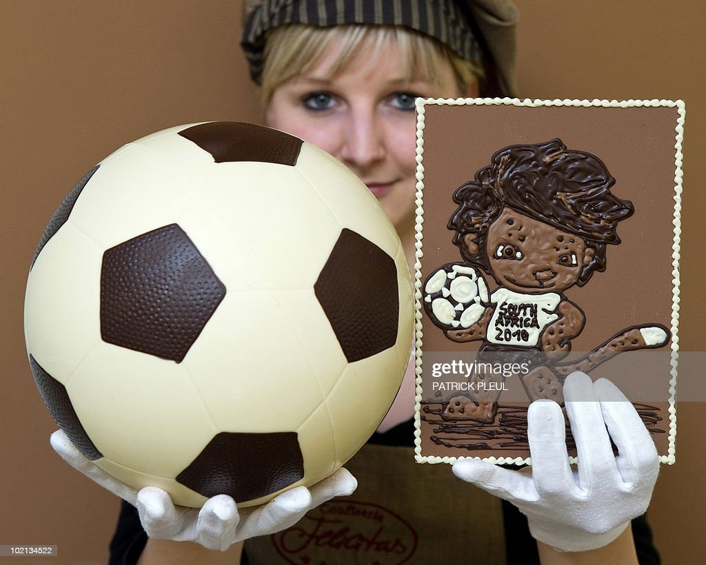 Nadine Kraemer, employee of the confectionery Felicitas, holds a chocolate-made football and an image of the FIFA Football World Cup's mascot Zakumi on June 15, 2010 at the company's plant in Hornow, eastern Germany. The chocolate manufacturer with 45 employees produces handmade pralines and chocolate since 1992.