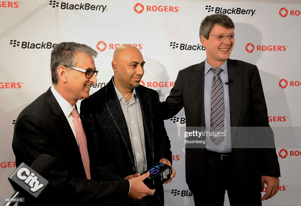 "Nadir Mohamed, president and chief executive officer of Rogers Communications Inc., left, and Thorsten Heins, president and chief executive officer of BlackBerry, right, present the first Blackberry Z10 to customer Harp Dhonsi at a Rogers store in Toronto, Ontario, Canada, on Tuesday, Feb. 5, 2013. Heins said early sales of the Z10 smartphone are ""encouraging"" and that users are switching from other platforms. Photographer: Aaron Harris/Bloomberg via Getty Images"