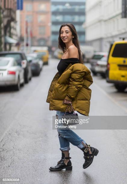 Nadja Ali wearing a black off shoulder Brandy Mellville shirt a Sabrina Dehoff necklace ripped Levis denim jeans net tights Wolford a mustard down...