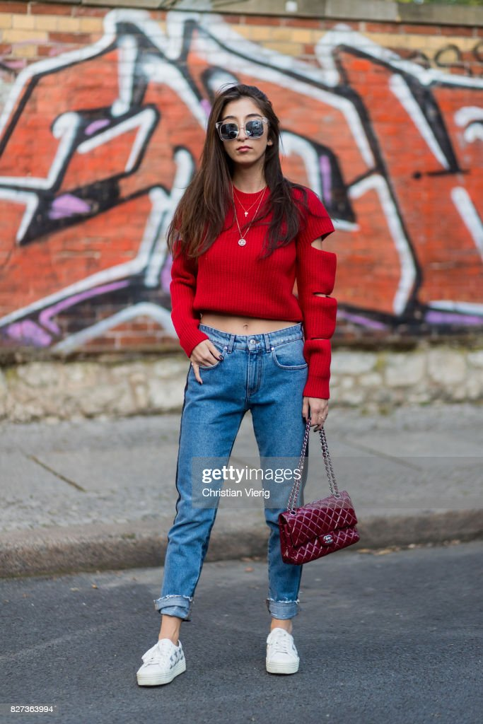 Nadja Ali wearing a red Dondup sweater, MSGM two tone denim jeans, red Chanel bag, Zero vintage sunglasses, Saint Laurent sneakers, Chanel necklace on August 7, 2017 in Berlin, Germany.