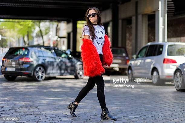 Nadja Ali wearing a white tshirt from Etre Cecile a black Acne denim jeans a red Asos fake fur jacket black Zara boots and black Celine sunglasses on...