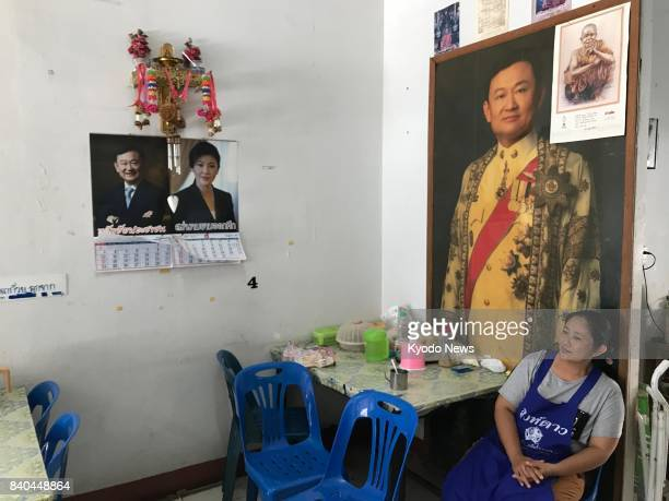 Naetdao Taepin sits in front of an enlarged photograph of former Thai Prime Minister Thaksin Shinawatra and calendars featuring Thaksin and his...