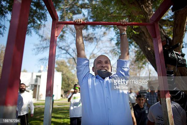 Naftali Bennett head of HaBayit HaYehudi Party the Jewish Home party does chinups after talking to students at a prearmy training school as he...