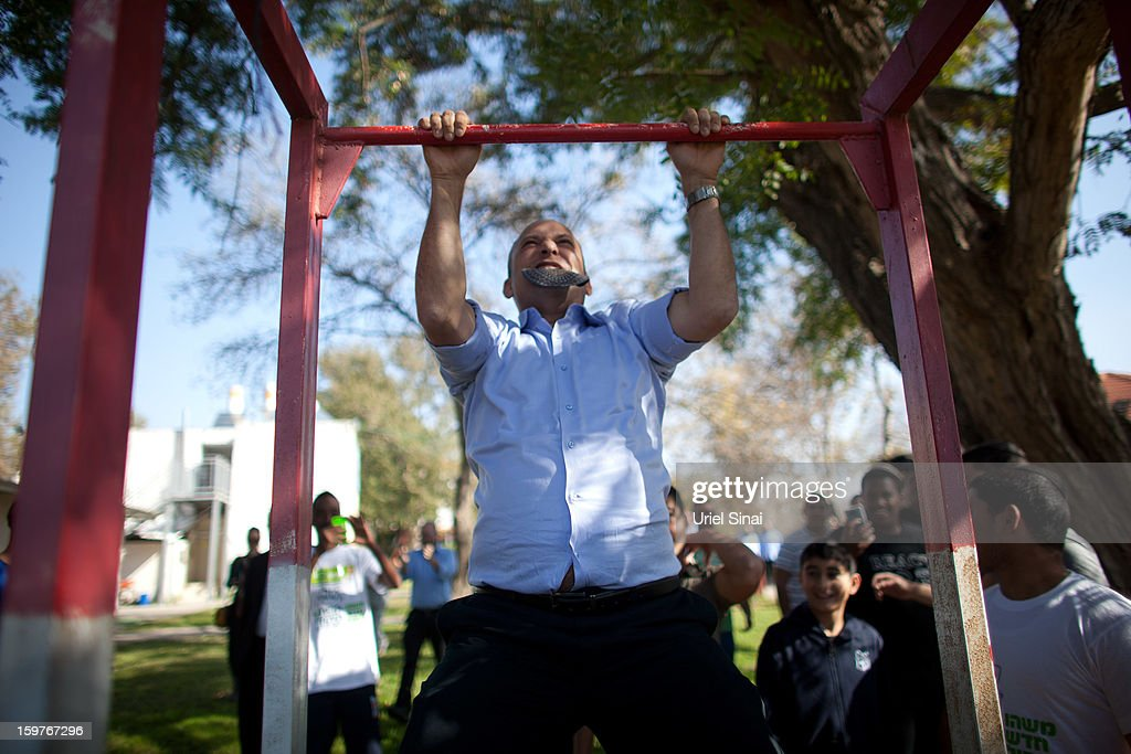 Naftali Bennett , head of HaBayit HaYehudi Party, the Jewish Home party, does chin-ups after talking to students at a pre-army training school as he campaigns in the Shapira Center on January 20, 2013 near Ashkelon, Israel. The religious Jewish Home party is challenging Benjamin Netanyahu's Likud party as Israel heads for a general election on January 22.