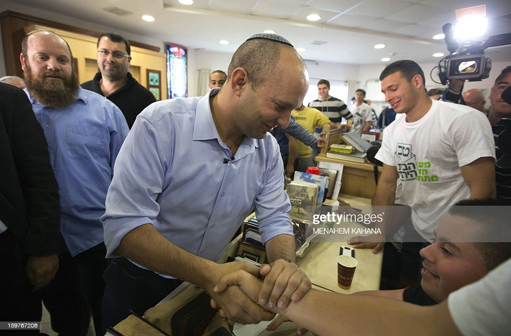 Naftali Bennett (C), head of the Israeli hardline national religious party, Jewish Home, shakes hands with students at a pre-military Yeshiva (religious school) in the village of Merkaz Shapira, 16 kilometres north-east of Ashkelon during a campaign visit on January 20, 2013. Israeli soldiers headed to the polls, two days ahead of a general election, the military said, as politicians made last-ditch appeals before nationwide voting gets underway on January 22.