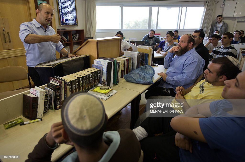 Naftali Bennett (L), head of the Israeli hardline national religious party, Jewish Home, talks to students at a pre-military Yeshiva (religious school) in the village of Merkaz Shapira, 16 kilometres north-east of Ashkelon during a campaign visit on January 20, 2013. Israeli soldiers headed to the polls, two days ahead of a general election, the military said, as politicians made last-ditch appeals before nationwide voting gets underway on January 22. AFP PHOTO/MENAHEM KAHANA