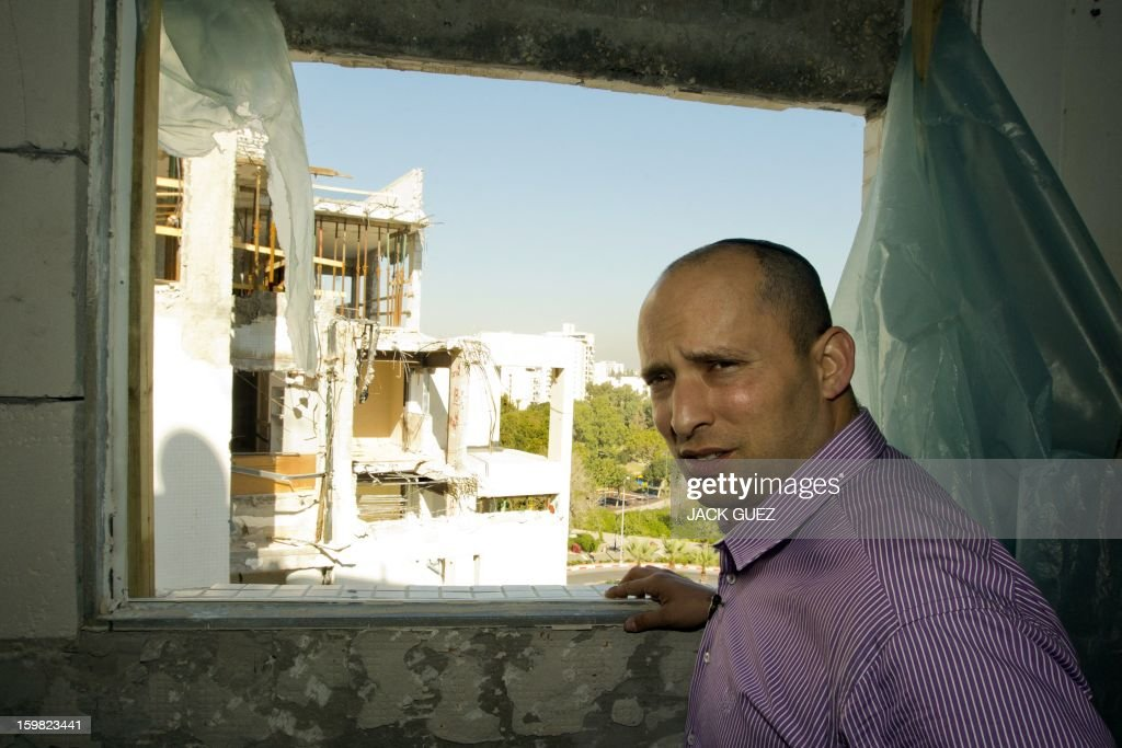 Naftali Bennett head of the Israeli hardline national religious party, Jewish Home, visits a destroyed apartment in a building that was hit by a rocket, fired from Gaza on November 20, 2012, during a campaign visit in the city of Rishon Letzion, near Tel Aviv, on January 21, 2013. With less than 24 hours until Israelis vote in general elections, party leaders were campaigning down to the wire ahead of a ballot seen returning Prime Minister Benjamin Netanyahu to office.