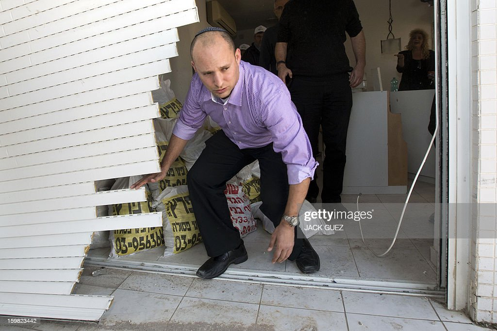 Naftali Bennett head of the Israeli hardline national religious party, Jewish Home, visits a destroyed apartment in a building that was hit by a rocket, fired from Gaza on November 20, 2012 during a campaign visit in the city of Rishon Letzion, near Tel Aviv, on January 21, 2013. With less than 24 hours until Israelis vote in general elections, party leaders were campaigning down to the wire ahead of a ballot seen returning Prime Minister Benjamin Netanyahu to office.