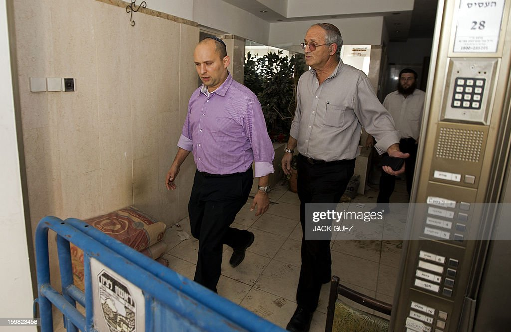 Naftali Bennett (L) head of the Israeli hardline national religious party, Jewish Home, visits a destroyed apartment in a building that was hit by a rocket, fired from Gaza on November 20, 2012 during a campaign visit in the city of Rishon Letzion, near Tel Aviv, on January 21, 2013. With less than 24 hours until Israelis vote in general elections, party leaders were campaigning down to the wire ahead of a ballot seen returning Prime Minister Benjamin Netanyahu to office. AFP PHOTO / JACK GUEZ