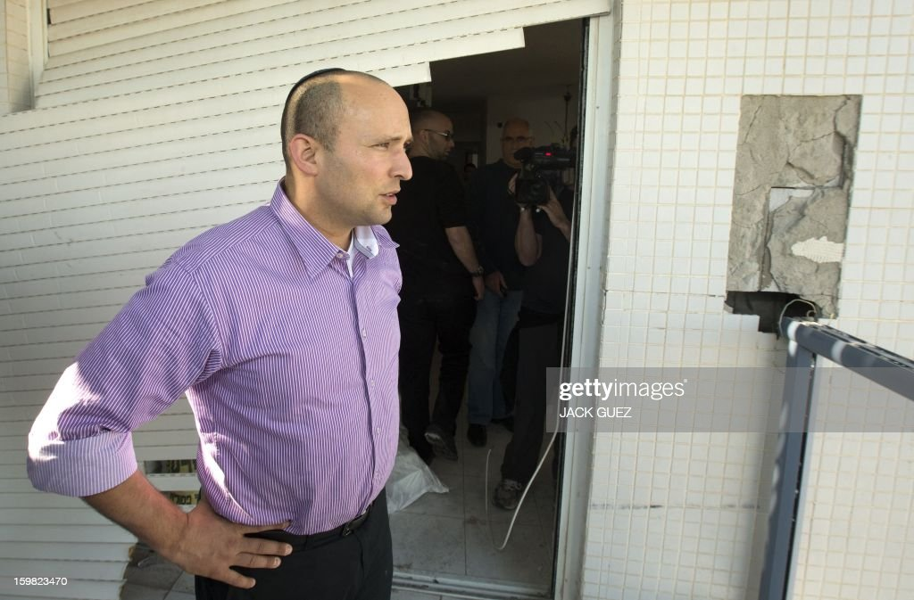Naftali Bennett (R), head of the Israeli hardline national religious party, Jewish Home, visits a destroyed apartment in a building that was hit by a rocket, fired from Gaza on November 20, 2012 during a campaign visit in the city of Rishon Letzion, near Tel Aviv, on January 21, 2013. With less than 24 hours until Israelis vote in general elections, party leaders were campaigning down to the wire ahead of a ballot seen returning Prime Minister Benjamin Netanyahu to office.