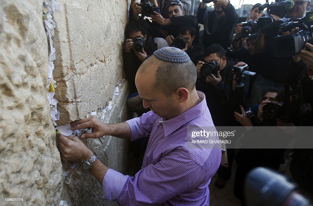 Naftali Bennett, head of the Israeli hardline national religious party, Jewish Home, visits the Western Wall, Judaism holiest site, and places a prayer during a tour in Jerusalem's old city on January 21, 2013. With less than 24 hours until Israelis vote in general elections, party leaders were campaigning down to the wire ahead of a ballot seen returning Prime Minister Benjamin Netanyahu to office.