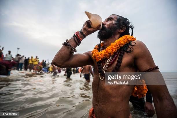 Naga sadhu blows a conch shell while bathing in the Ganges river during the Shahi Snan of Basant Panchami the main bathing day of Maha Kumbh Mela