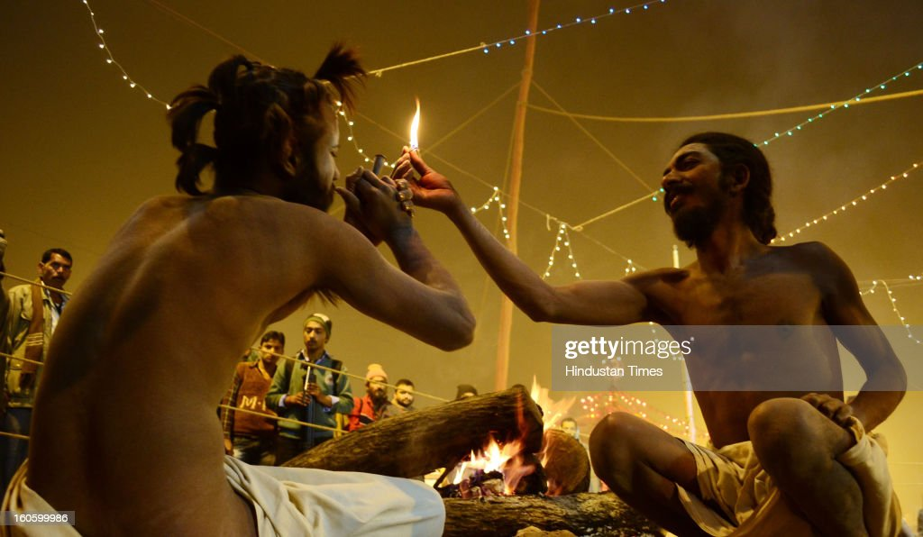 A Naga Sadhu gets ready for a round of smoking 'Chillum' even as another strikes the match to light it up in their camp in Kumbh Mela area on February 3, 2013 in Allahabad, India. The mega religious fair is held once in 12 years in Allahabad and the third official bathing is set to take place on 'Mauni Amawasya' on February 10, 2013 during which millions of pilgrims are expected to converge from all over India and even abroad.