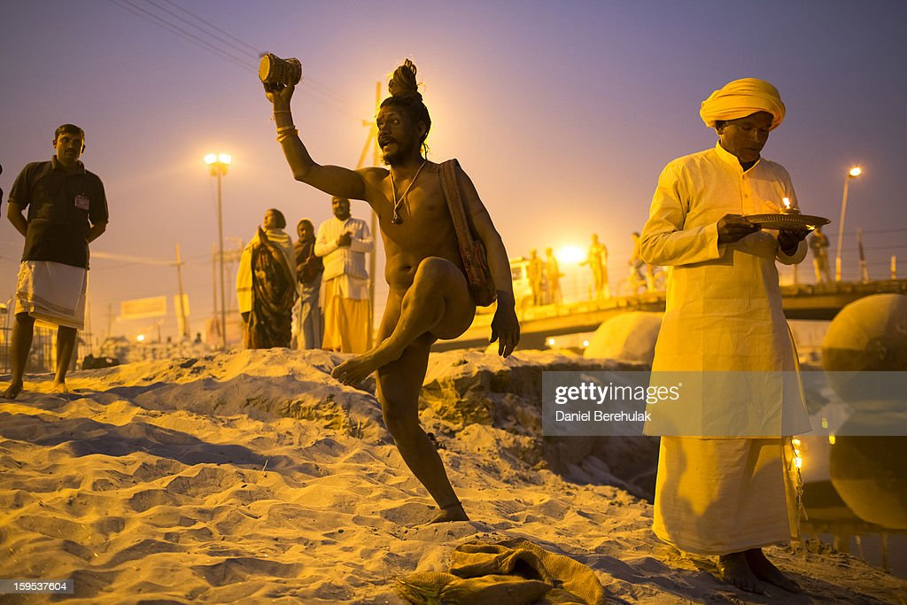 A naga sadhu performs during an aarti ceremony on the banks of the Ganges river during the Maha Kumbh Mela on January 15, 2013 in Allahabad, India. The Maha Kumbh Mela, believed to be the largest religious gathering on earth is held every 12 years on the banks of Sangam, the confluence of the holy rivers Ganga, Yamuna and the mythical Saraswati. The Kumbh Mela alternates between the cities of Nasik, Allahabad, Ujjain and Haridwar every three years. The Maha Kumbh Mela celebrated at the holy site of Sangam in Allahabad, is the largest and holiest, celebrated over 55 days, it is expected to attract over 100 million people.